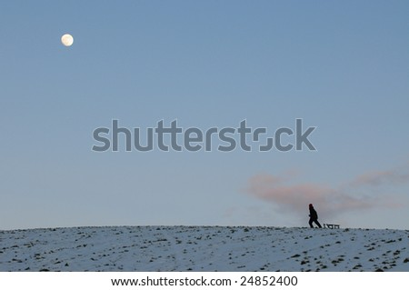child pulling toboggan over hill of snow in moonlight - stock photo