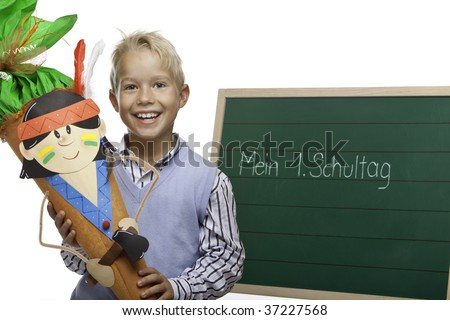 child (pupil) ist standing beside chalkboard having its first schoolday - stock photo
