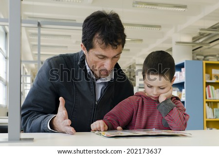 Child pupil with parent or teacher reading a book in public library.  - stock photo