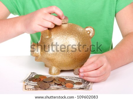 child putting money in a golden piggy bank - stock photo