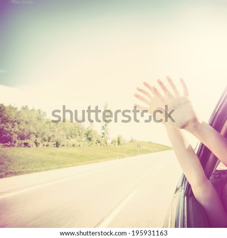 Child putting their hands out of the car window  - stock photo