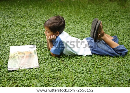 Child reading a book on the lawn - stock photo
