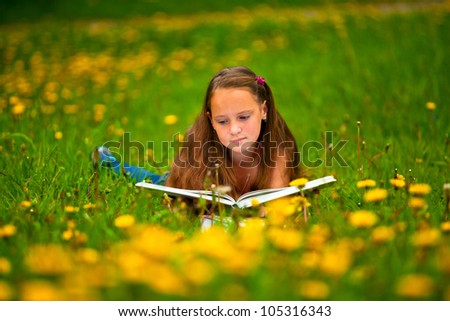 Child reading a book while lying in the grass - stock photo