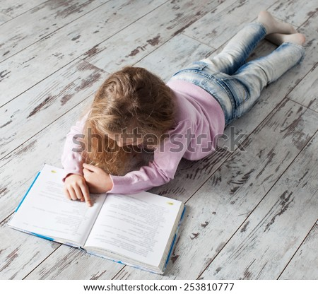 Child reading book at home. Girl doing homework - stock photo
