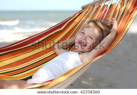 child relaxing in a hammock on the sea beach - stock photo