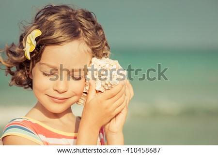 Child relaxing on the beach against sea and sky background. Summer vacation and travel concept - stock photo