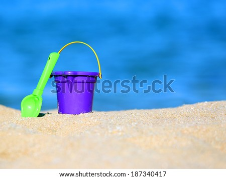 child resort - bucket and shovel in sand on seashore - stock photo
