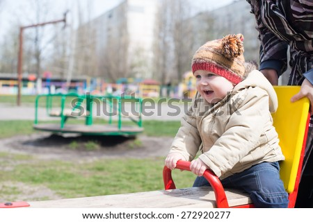 child ride on swings against summer nature. - stock photo
