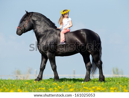 Child riding a black horse in pasture. - stock photo