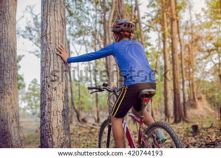 Child riding a mountain bike in the woods. - stock photo