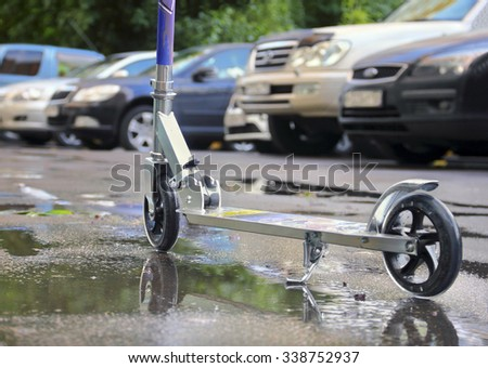 Child riding metal scooter on a wet paved pathway against the background of the row of cars - stock photo