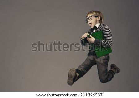 child running back to school, funny kid portrait, jumping smart schoolboy with glasses and book - stock photo