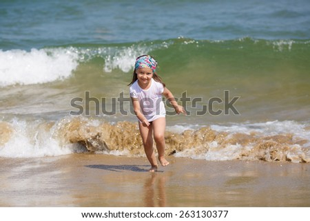 Child runs along the beach on a background of a sea wave. Shallow depth of field. Focus on model. - stock photo