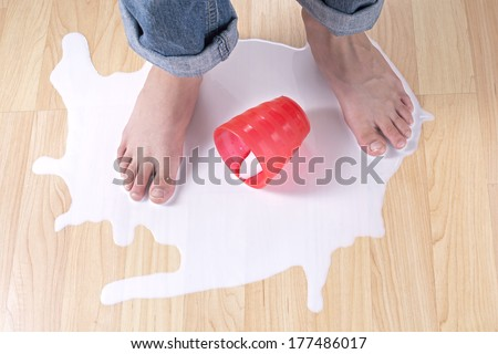 Child's bare feet standing in puddle of spilled milk on wood floor with red cup - stock photo