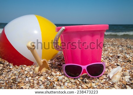 Child's bucket, ball, glasses  and other toys on tropical beach against blue sky - stock photo