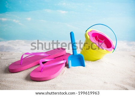 Child's bucket, spade and flip flops on tropical beach against blue sky  - stock photo