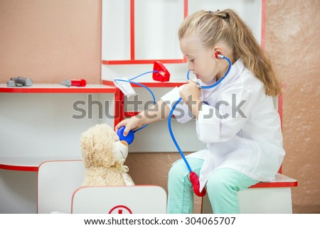 child's doctor examines a teddy bear - stock photo