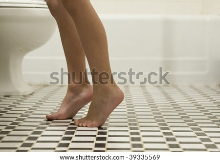 Child's Feet and Legs in Bathroom - stock photo