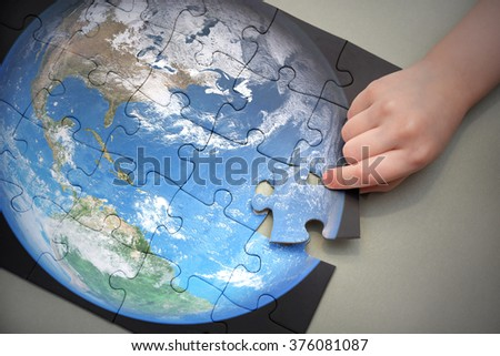 Child's hand adds puzzle with planet earth concept. Elements of this image furnished by nasa - stock photo