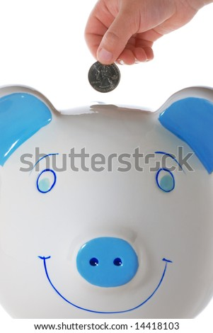 Child's hand dropping a quarter in a white and blue ceramic piggy bank, isolated on white - stock photo