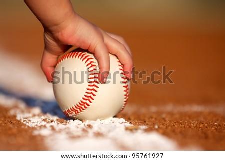 Child's hand grabbing a baseball - stock photo
