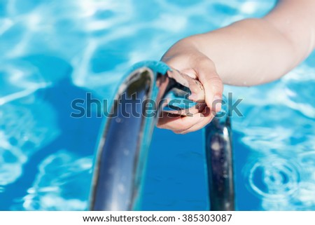 Child's hand holding a handrail in swimming pool - stock photo