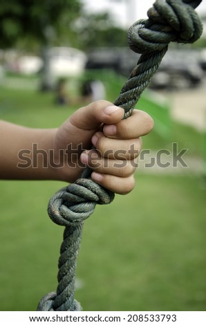 Child's hand holding a rope in the grass. - stock photo