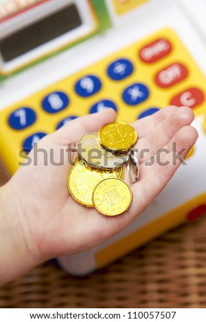 Child's Hand Holding Pretend Coins Next To Toy Cash Register - stock photo