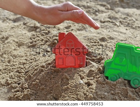 Child's hand over the house in a sandbox. Hand as a roof over the house. Bright plastic toys in the sandbox or on the beach. Sandbox, children, hand, home, house, buy, purchase, housing, business. - stock photo
