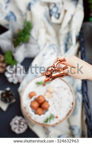 Child's hand placing a reindeer figurine for a christmas dinner table setting. Shallow focus. Toned photo. - stock photo