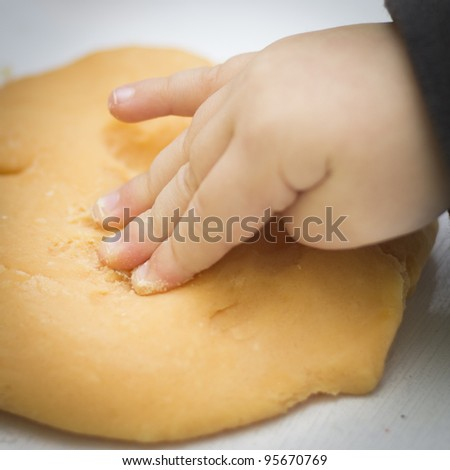 Child's hand presses playdough - stock photo