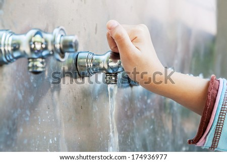 Child's hand with drinking water running from tap water - stock photo