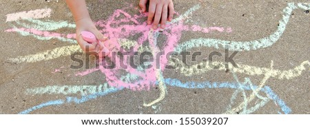 Child's hands drawing with chalk on sidewalk - stock photo