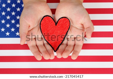 Child's hands hold red paper heart against American flag.  - stock photo