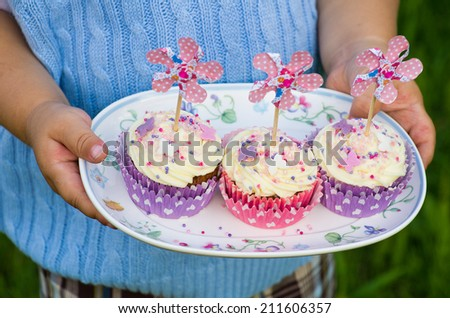 Child's hands holding a plate with pink and purple cupcakes with pinwheels - stock photo