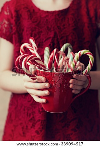 Child's hands holding Christmas candy canes - stock photo