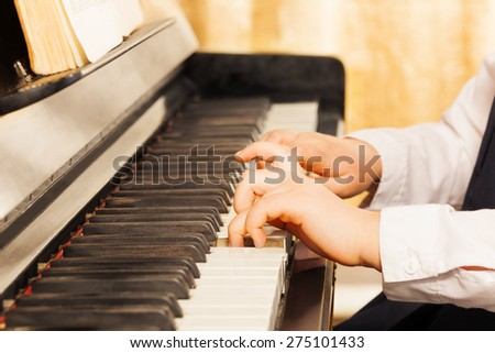 Child's hands playing on the piano-keys - stock photo