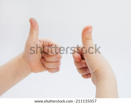 Child's hands showing positive sign, white background - stock photo