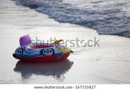 Child's inflatable swimming aid on beach at sunset - stock photo