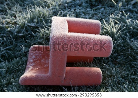 Child's Red plastic chair covered in early morning frost - stock photo