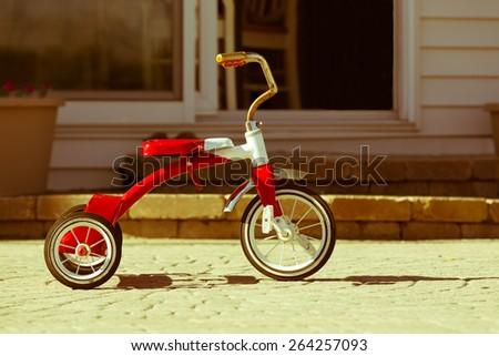 Child's rusted favorite cherished red tricycle standing ready and waiting for its owner to arrive on paving outside a house - stock photo