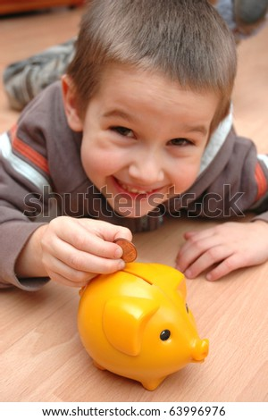 Child save money into the piggy bank - stock photo