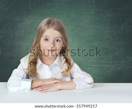 Child school girl in white shirt sitting at the table on blackboard green color background.Elementary school study concept. - stock photo