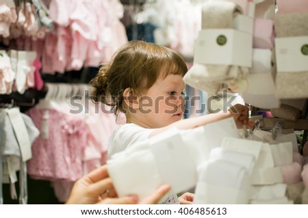 Child searches clothes while shopping - stock photo
