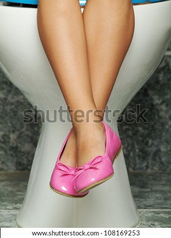 Child seated on toilet - stock photo