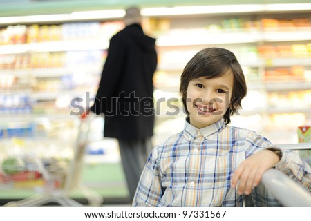 Child shopping in supermarket - stock photo