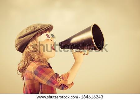 Child shouting through vintage megaphone. Cinema concept. Retro style - stock photo
