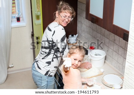 Child showing hand with dough when kneading with mother - stock photo