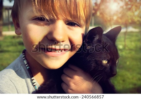 child shows  with affection his  black cat - stock photo
