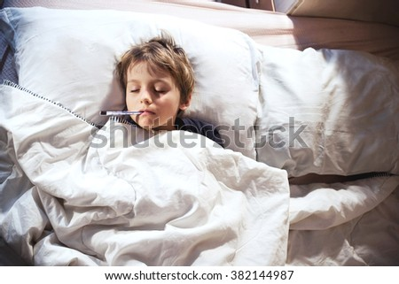 child sick in bed with fever and thermometer - stock photo